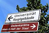 Auf diesem Bild sieht man ein Schild für die Stasi-Gedenkstätte. Darüber ein Schild zur Uni.