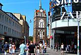 Auf diesem Bild sieht man das Kröpeliner Tor, davor Geschäfte.