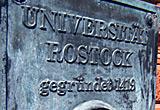 Auf diesem Bild sieht man ein Bronzeschild mit dem Logo der Uni Rostock.